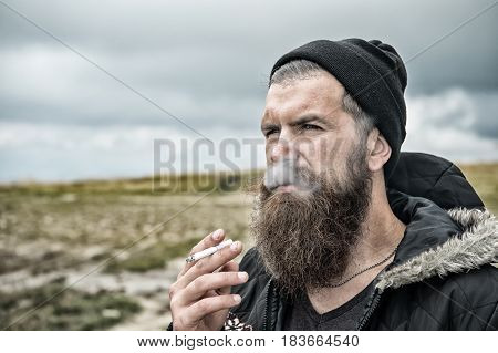 Man With Beard Smoking Cigarette At Mountain, Cloudy Sky
