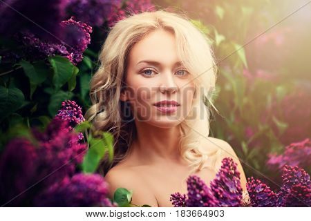 Smiling Woman Fashion Model Outdoors. Pretty Face Blonde Hair and Flowers