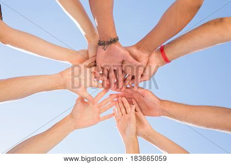 Directly below shot of friends stacking hands against clear sky
