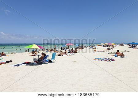 MIAMI BEACH USA - JULY 27: People enjoy swimming in South Beach on July 272010 in Miami Beach USA. In 1870 Henry and Charles Lum purchased the area and his daughter Taylor named it South Beach.