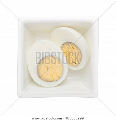 Hard boiled egg in a square bowl isolated on white background