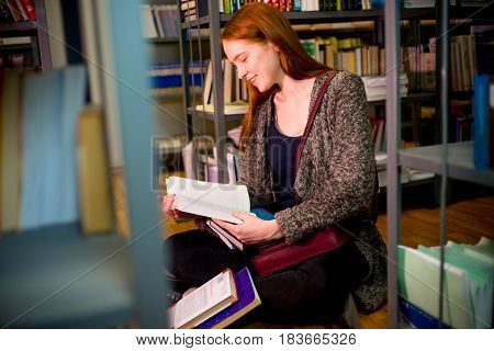 College student reading book in university library
