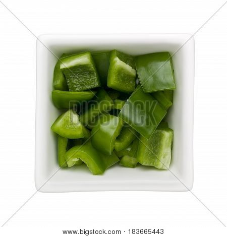 Diced green bell pepper in a square bowl isolated on white background