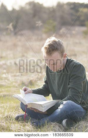 Man reading Bible in open field outdoors