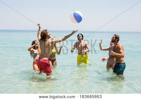 Friends playing with ball in sea on sunny day