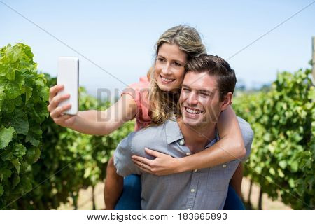 Happy young couple taking selfie while piggybacking at vineyard against blue sky