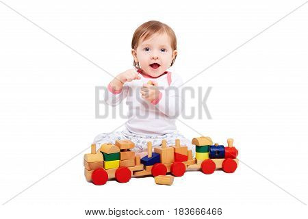 Beautiful baby girl playing a wooden train, isolated on a white background