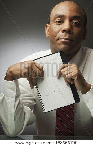 African businessman holding datebook