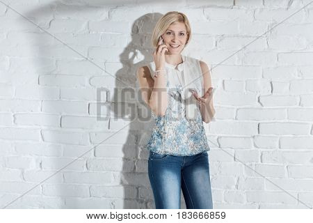 Happy blonde woman talking on mobilephone, smiling.