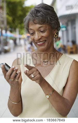 African woman text messaging on cell phone