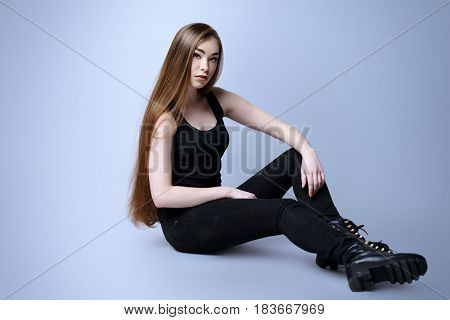 Vogue shot. Full length portrait of a fashionable model with beautiful long hair posing at studio in casual black clothes.
