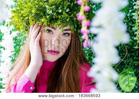 Spring girl portrait. Tender young woman in a wreath of green plants. Beauty, fashion concept. Cosmetics and perfumery.