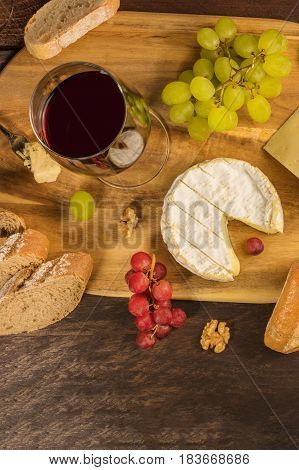 An overhead photo of a glass of red wine with a selection of cheeses, bread, grapes, and a place for text