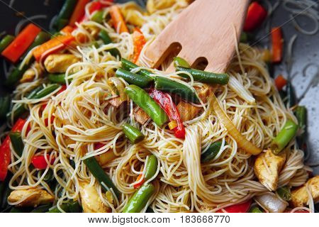 Delicious rice noodle stewing with vegetables on wok