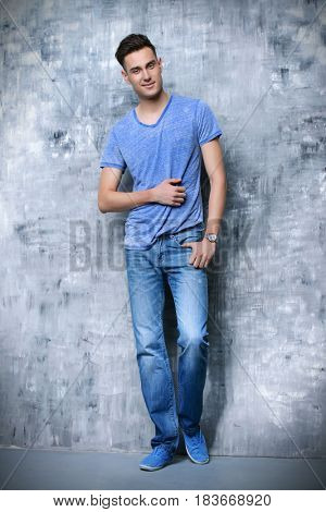 Full length portrait of a positive smiling young man in casual clothes. Studio shot.