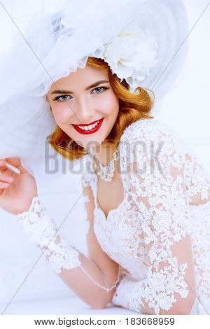 Charming bride wearing elegant lace dress and broad-brimmed hat is happy and laughing. Wedding. Beauty, fashion concept.