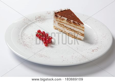 Tiramisu On A White Plate Decorated With Red Currants