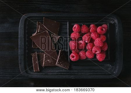 Dark and milk chopping chocolate and chips on old plate with fresh raspberries in black wood box over black burnt wooden background. Top view with space. Chocolate dessert concept