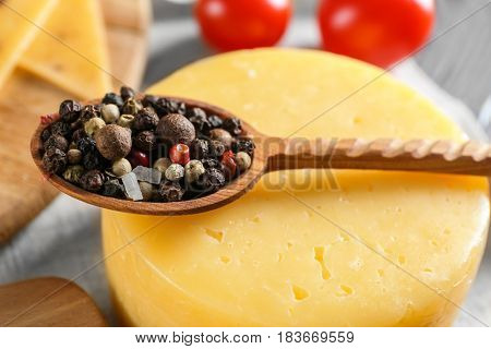 Wooden spoon with mixture of peppers on cheese head