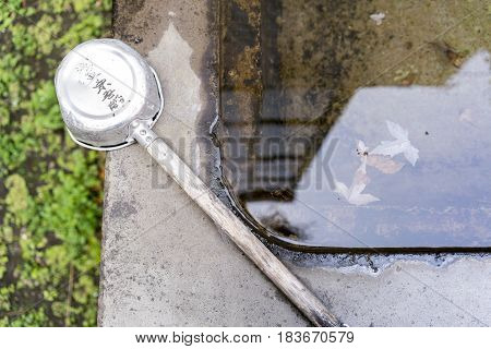 Stone water basin with old ladle at Shinto shrine in Tokyo Japan