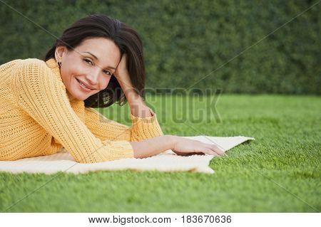Hispanic woman laying in grass