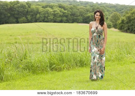 Hispanic woman in evening gown in field