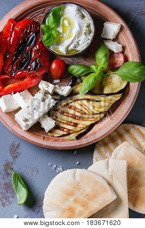 Ingredients for making pita bread sandwiches. Grilled vegetables, basil and feta cheese with flat bread on terracotta plate over gray texture background. Healthy fast food concept. Top view
