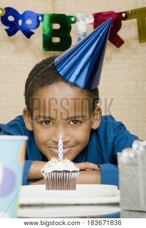 African boy with cupcake at birthday party