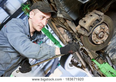 Auto repair service. Mechanic works with car suspension
