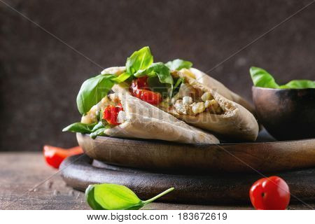 Pita bread sandwiches with grilled vegetables paprika, eggplant, tomato, basil and feta cheese served on black chopping board over dark wooden background. Healthy fast food concept. Close up