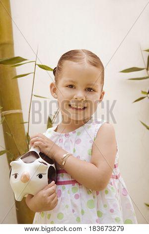 Hispanic girl holding piggy bank