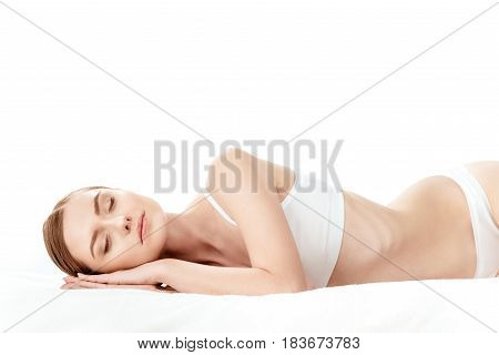 Beautiful Young Woman In White Underwear Sleeping Isolated On White, Skin Care Concept