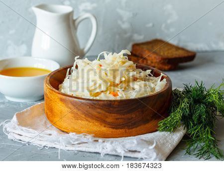 Sauerkraut in wooden bowl with bread oil and dill. Love for a healthy vegan food concept