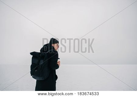 young hipster guy dressed in black in the winter on the frozen lake with a cup of coffee in hand and looking into the void