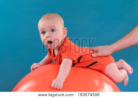 Cute Baby Lying On The Orange Fitball On The Blue Background. Concept Of Caring For The Baby's Healt