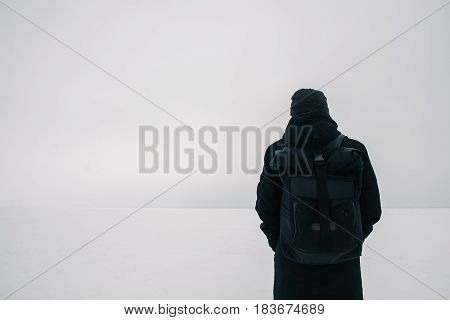 back hipster young man with a black backpack traveling in winter on the frozen pond
