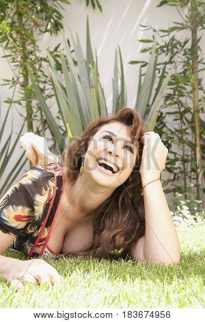 Laughing Hispanic woman laying in grass