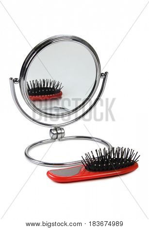 Hairbrush and mirror on a white background