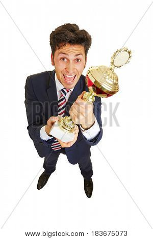 Cheering business man with a big trophy in his hands