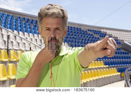 People, sport and soccer concept - man referee whistling pointing