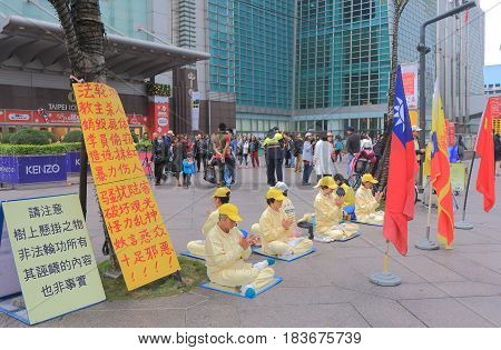 TAIPEI TAIWAN - DECEMBER 6, 2016: Unidentified people practice Falun Gong at Taipei 101. Falun Gong is a Chinese spiritual practice viewed as a potential threat by the communist party China.
