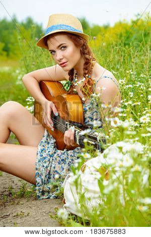 Beautiful romantic girl with a guitar on a country road on a sunny summer day.