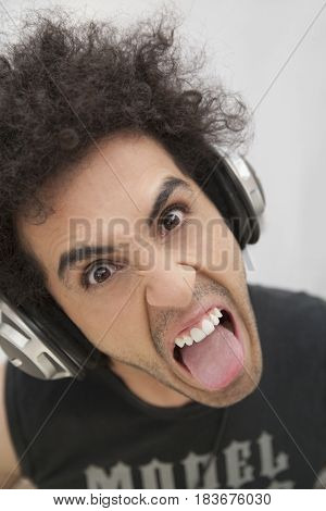 Hispanic man in headphones grimacing