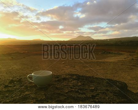 Beautiful view overlooking rusty red desert, distant mountains in a rose mist and slightly cloudy dawn sky. Fuerteventura island, Canaries, Spain.