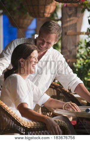 Laughing Caucasian couple in restaurant