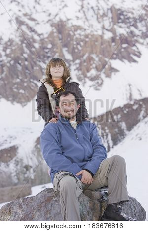 Hispanic father and daughter sitting on rock in snow