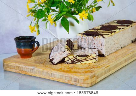 Delightful cheesecake with Oreo cookies. Background - vase with flowers and ceramic cup. Professional bakery