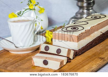 Three-layer chocolate cake, decorated with chocolate patterns. Beautiful cake Three-colate. Background - white vase with flowers and porcelain cup with hot tea. Professional bakery