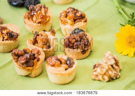Professional baking. Small portioned tartlet cakes with filling of nuts and dried fruits. Background -prune