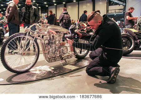 St. Petersburg Russia - 15 April, A photographer at a motorcycle,15 April, 2017. International Motor Show IMIS-2017 in Expoforurum. Motorcycles and motoconcepts presented at St. Petersburg Motor Show.